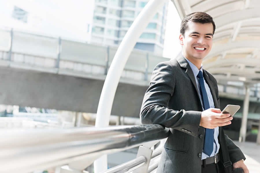 Happy smiling hispanic businessman using mobile phone outdoors in the city