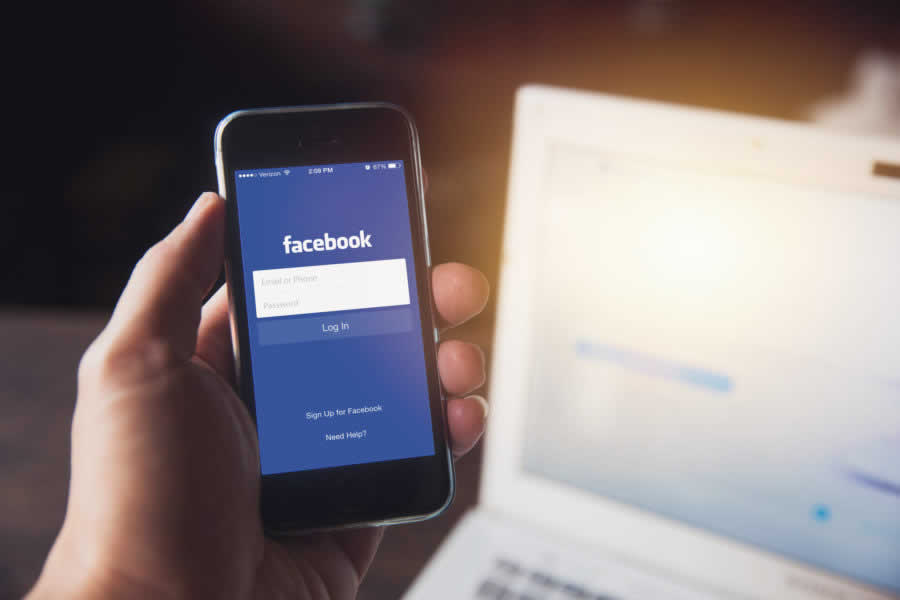 Facebook App on iPhone with computer laptop background closeup male hand hold social network on smart device concept.