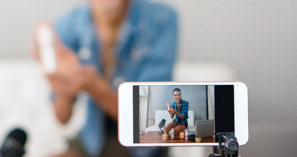 celular em primeiro plano gravando uma mulher segurando um produto - redes sociais na crise do coronavírus