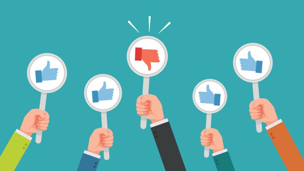 mãos segurando cartazes de like e deslike - análise de sentimento em redes sociais