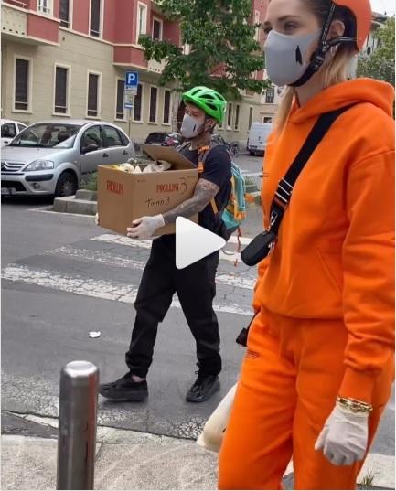 mulher com máscara e luvas, homem atras com caixa de alimentos - papel dos influenciadores