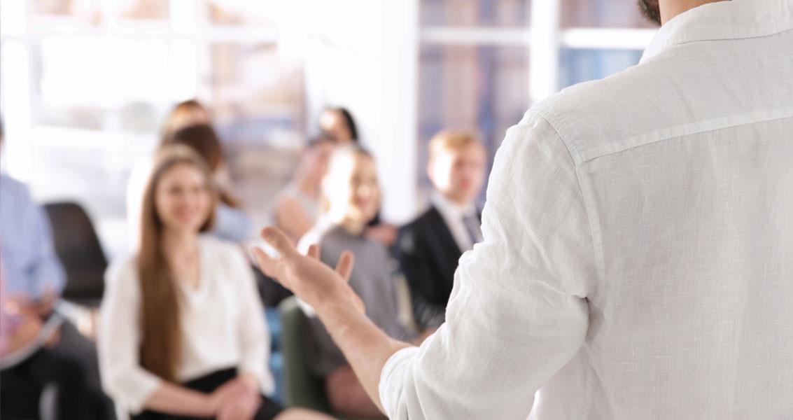 executivo gesticula em frente a plateia - competências de comunicação